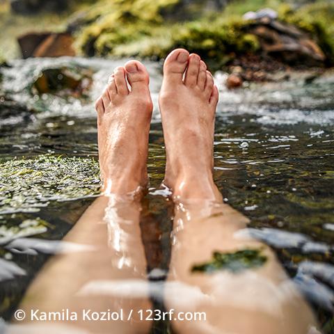 Beine, die im Wasser liegen