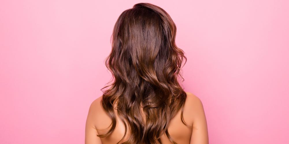 Gelockte, braune Haare von hinten auf rosa Hintergrund.