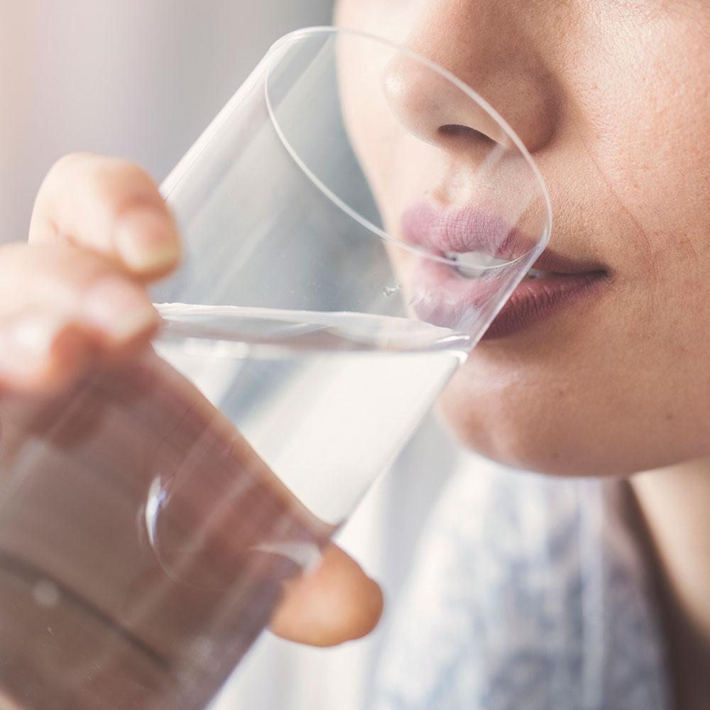 Nahaufnahme Frau, die ein Glas Wasser trinkt.