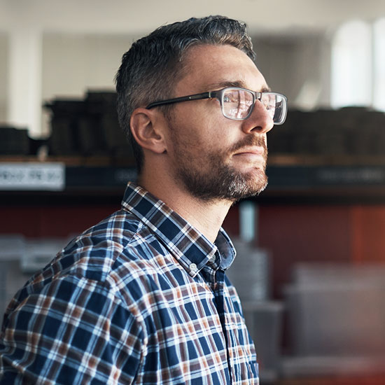 Man with glasses, looking into the distance.