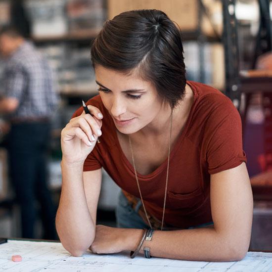 Frau, die sich konzentriert über einen Plan beugt mit einem Stift in der Hand.