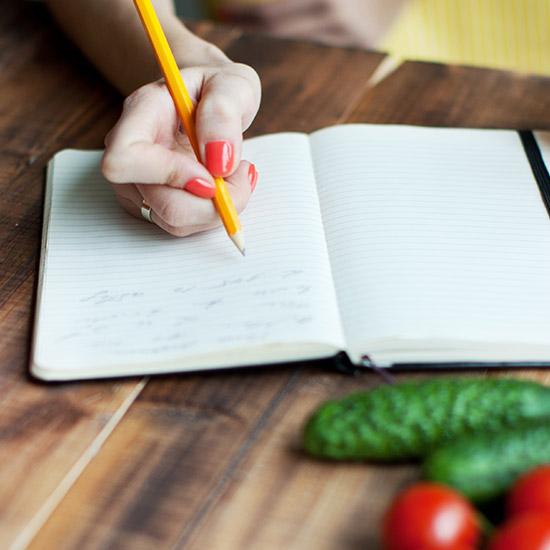 Frau schreibt Speiseplan in Buch