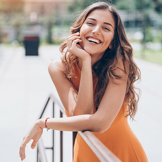 Glückliche Frau in orangem Kleid