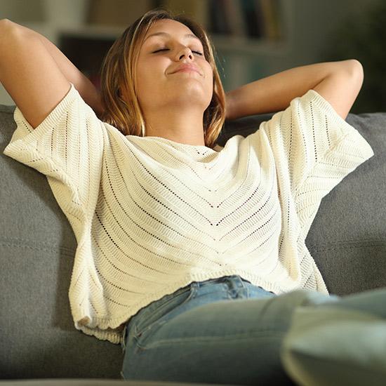Frau entspannt sich auf Sofa