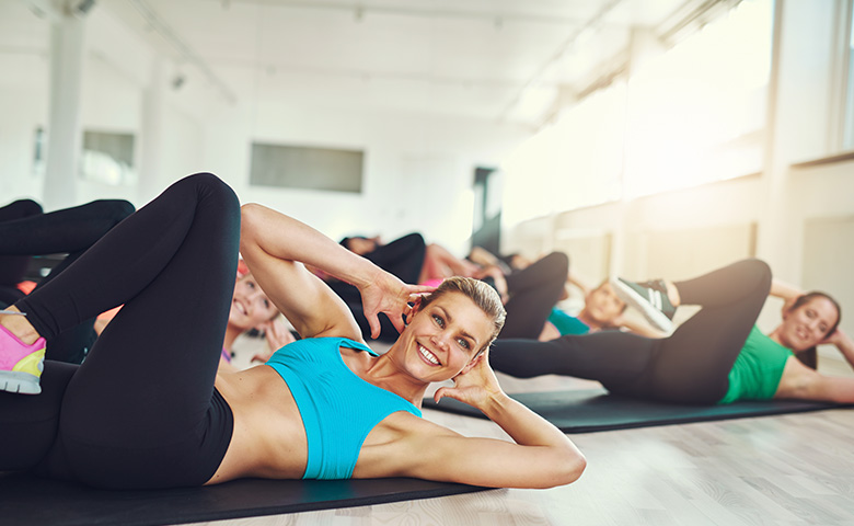 Frau liegt am Boden und macht Fitness-Übungen