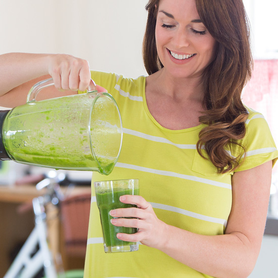 Woman pouring herself a smoothie