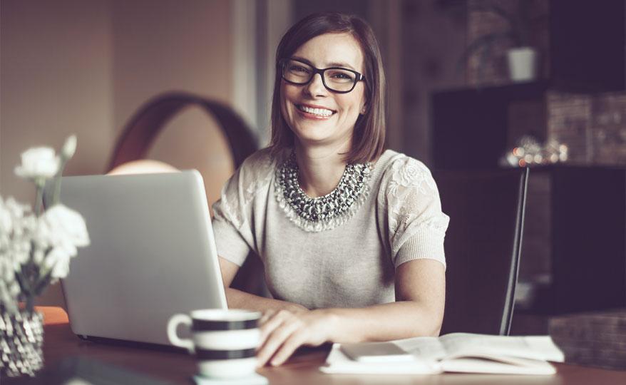 Frau, die an Computer arbeitet und in die Kamera lächelt.