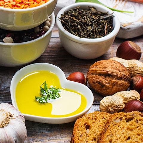 Ein gedeckter Tisch mit Nüssen, Vollkornprodukten, Ölen und Linsen