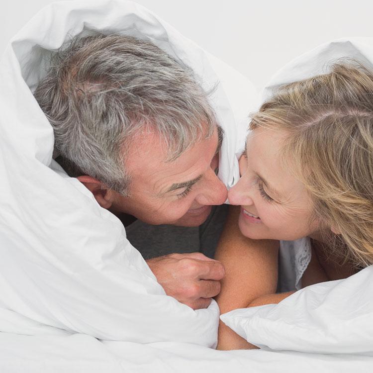 Mann und Frau liegen unter Bettdecke und schauen sich an