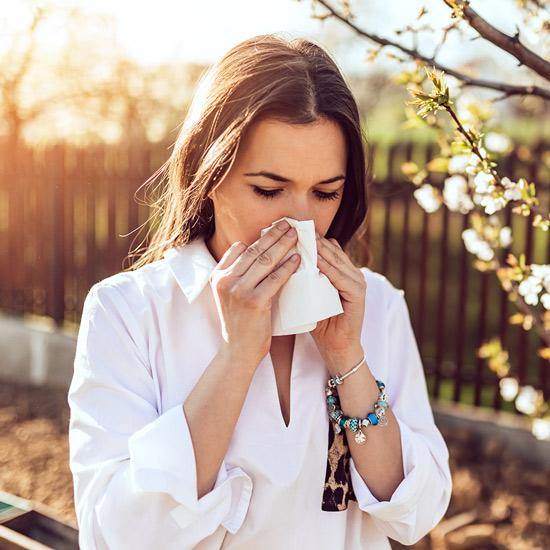 Frau mit Taschentuch und Erkältung