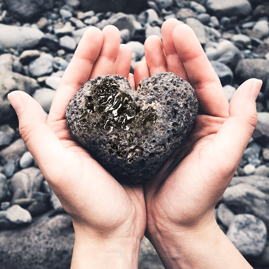 Hands holding a black stone