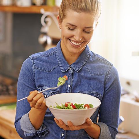 Frau, die gerade Salat aus einer Schüssel isst.
