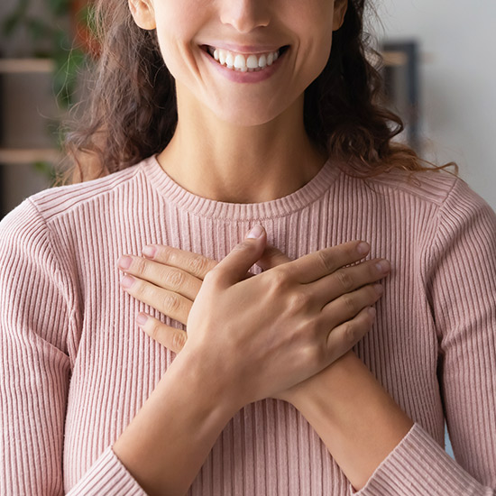 Frau legt Hände über ihr Herz