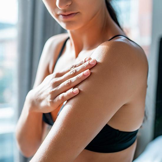 Frau berührt mit Hand ihre Haut